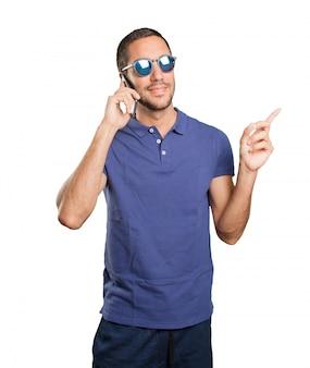 Cool junger Mann mit einem Handy auf weißem Hintergrund