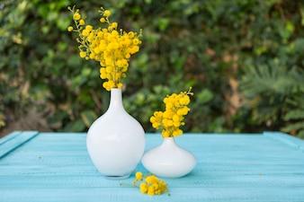 Dekorative Vasen mit Blumen auf dem blauen Oberfläche