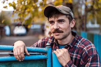 Der Mann im Dorf in einer Mütze mit einem Schnurrbart
