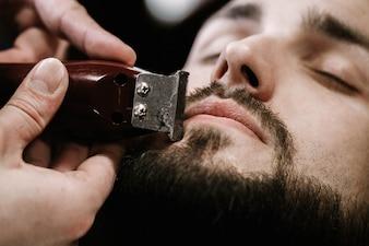 Der Mensch schließt seine Augen, während der Barbier seinen schwarzen Bart formt