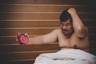 Der müde Mann wird wütend, wenn der Wecker ihn morgens aufwacht.