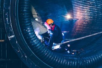Der Schweißer in der Maschinenarbeit macht die Schweißarbeiten