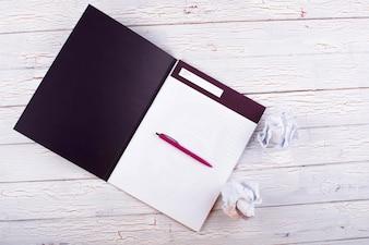 Der Stift, die Notizbücher und die Papiere stehen auf dem Tisch