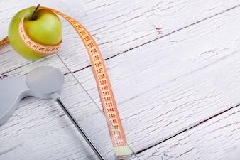 Der Zentimeter steht in der Nähe eines grünen Apfels