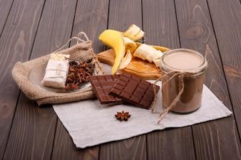 Detox cocktail mit zimtstangen, bananen und schokolade liegen auf dem tisch