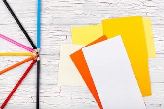 Die farbigen Bleistifte und Papiere stehen auf dem Tisch