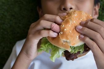 Die Hand des Jungen, die einen Hamburger hält