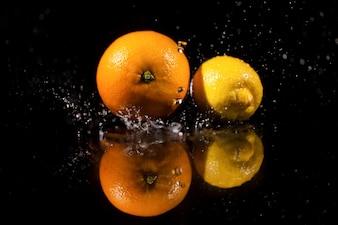 Die Orange und Zitrone stehen auf dem schwarzen Hintergrund
