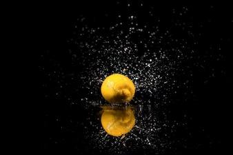 Die Zitrone mit Tropfen steht auf dem schwarzen Hintergrund
