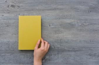 Draufsicht auf die Hand, die ein Buch öffnet