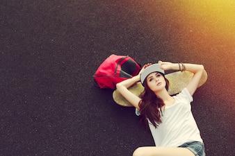 Draufsicht der Frau auf dem Boden mit Skateboard liegend