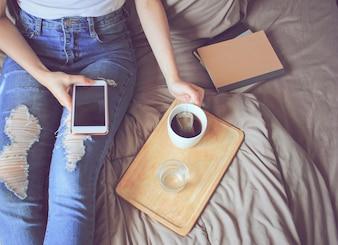 Draufsicht der jungen Frau in Freizeitkleidung mit Smartphone auf dem Bett mit Tee und Notebook, Lifestyle-Konzept