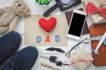 """Draufsicht Happy Father Day mit Reise-Konzept.Red Herz und Wort """"DAD mit Papier auf rustikalen hölzernen Hintergrund. Zubehör mit, Pass, Flugzeug, Schnurrbart, Vintage-Fliege, Stift, Geschenk, weiß Handy, Schuhe und Notebook."""