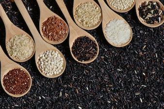 Draufsicht verschiedenen Reis auf hölzernen Schaufel mit schwarzen Riceberry Hintergrund, verschiedene Reis Bio auf Holz Löffel Sammlung