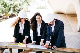 Drei Architekten mit Plan am Tisch