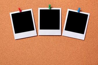 Drei polaroid Fotoabzüge auf einem Korkenanschlagtafel