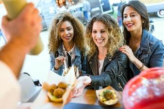 Drei schöne junge Frauen besuchen Markt auf der Straße.