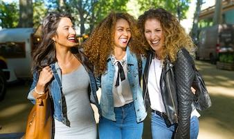 Drei schöne junge Frauen zu Fuß und reden auf der Straße.