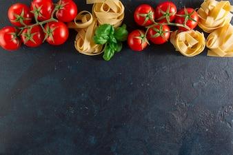 Dunkler Hintergrund mit Spaghetti und Tomaten