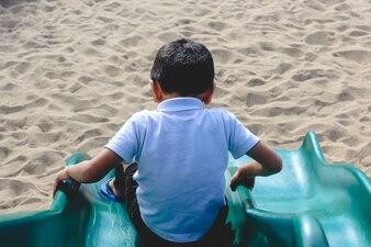Ein kleiner Junge, der einen Spielplatz hinunterrutscht