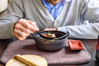 Ein Mann isst Miso-Suppe in einem traditionellen japanischen Restaurant