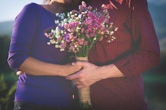 Ein romantisches Paar hält Valentines Geschenk und Blumen, Vintage Ton