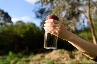 Eine Wasserflasche von einer weiblichen Hand auf Natur Hintergrund gehalten.
