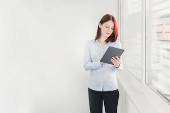 Elegante weibliche Arbeiter durchsuchen Tablette