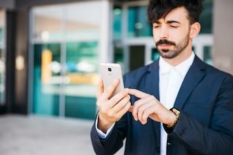 Eleganter Geschäftsmann, der Smartphone betrachtet