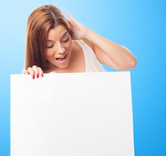 Entsetzte Frau mit leeren Plakatwand