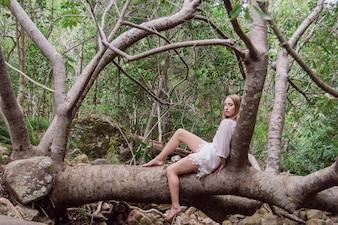 Entspannt Frau auf einem Stamm sitzt