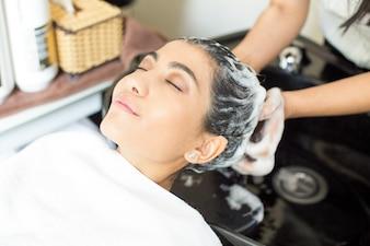 Entspannte junge Frau genießt das Haar waschen im Salon