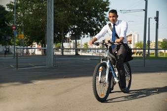 Erfolgreicher lateinischer Geschäftsmann, der Fahrrad zur Arbeit reitet