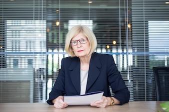Ernste Frau arbeitet mit Dokumenten im Amt
