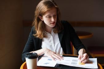 Ernste Geschäftsfrau, die mit Papieren im Café arbeitet