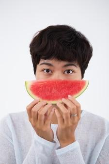 Ernste junge asiatische Frau hält Wassermelone