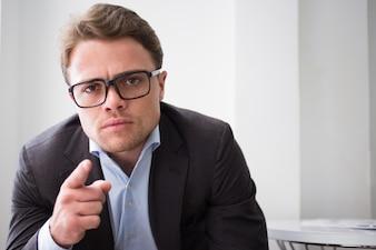 Ernster junger Geschäftsmann zeigt auf Kamera