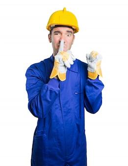 Ernsthafte Arbeiter mit Stille Geste auf weißem Hintergrund