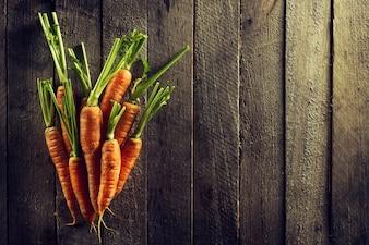 Essen Bio-Gemüse Bunte Hintergrund. Leckere frische Karotten auf Holztisch. Draufsicht mit Kopierraum. Gesundes Lebenskonzept.