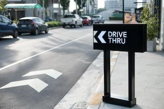Fahren Sie durch Zeichen mit Ladenhintergrund.
