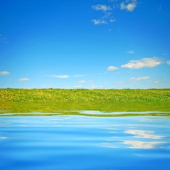 Feld von einem See gesehen