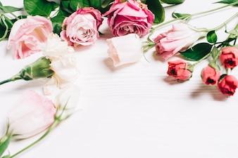 Feminine Schreibtisch Arbeitsbereich Rahmen mit rosa Rosen und Blütenblätter auf weißem Holz Hintergrund. Flache Lage, Draufsicht. Blumenhintergrund. Frauentag, Muttertag.