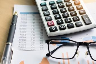 Finanzielle Charts auf dem Tisch mit Laptop, Taschenrechner, Stift und Gläser Business-Konzept