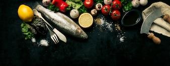 Fisch mit Gemüse auf einem schwarzen Hintergrund
