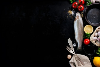 Fisch mit Gemüse und Besteck auf einem schwarzen Hintergrund