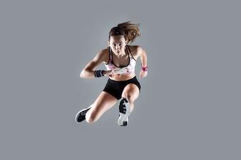 Fit und sportliche junge Frau springt auf weißem Hintergrund.