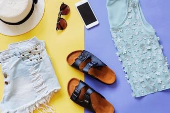 Flat lay Stil der Sommerkleidung und Zubehör auf buntem Hintergrund