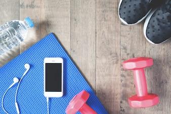 Flat lay von Handy mit Kopfhörer und Sportgeräte auf Holz Hintergrund. Workout und Fitnessartikel, Draufsicht