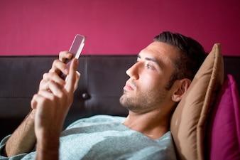 Fokussierte Mann mit Smartphone auf Sofa am Abend