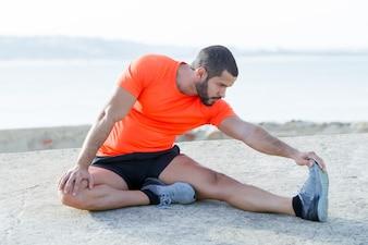 Fokussierter starker sportlicher Mann, der Beine draußen dehnt